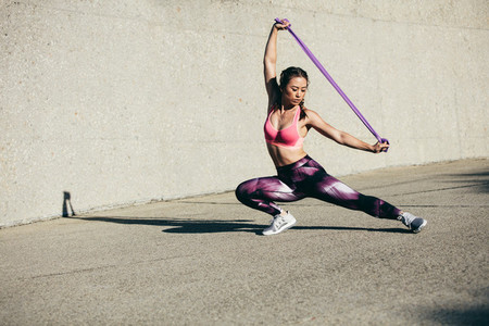 Strong woman stretching using a resistance band