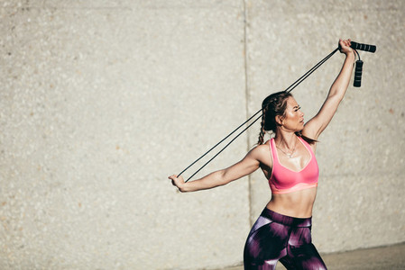 Strong woman in stretching with skipping rope