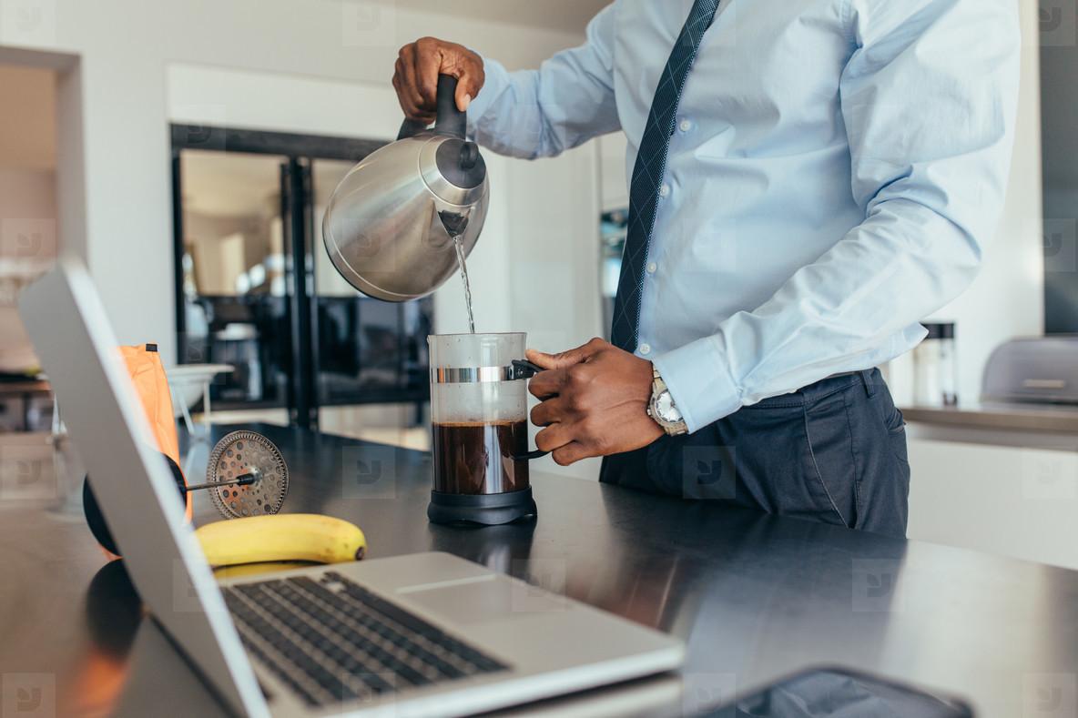 Businessman preparing coffee at home
