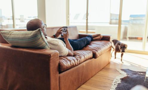 Man lying on lounge using mobile phone