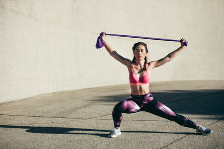 Woman exercises with resistance band