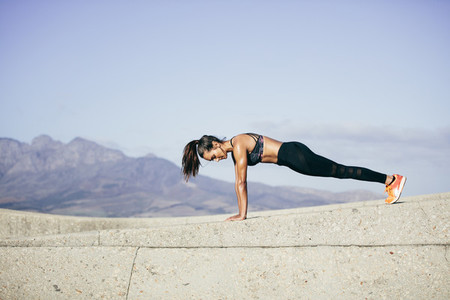 Tough young woman doing pushups outdoors