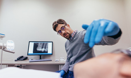 Stomatologist examining teeth of female patient