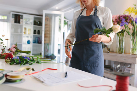 Skillful woman making bouquet in workshop
