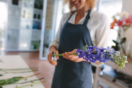 Female florist creating bouquet of flowers