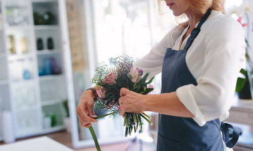 Skillful female florist creating bouquet