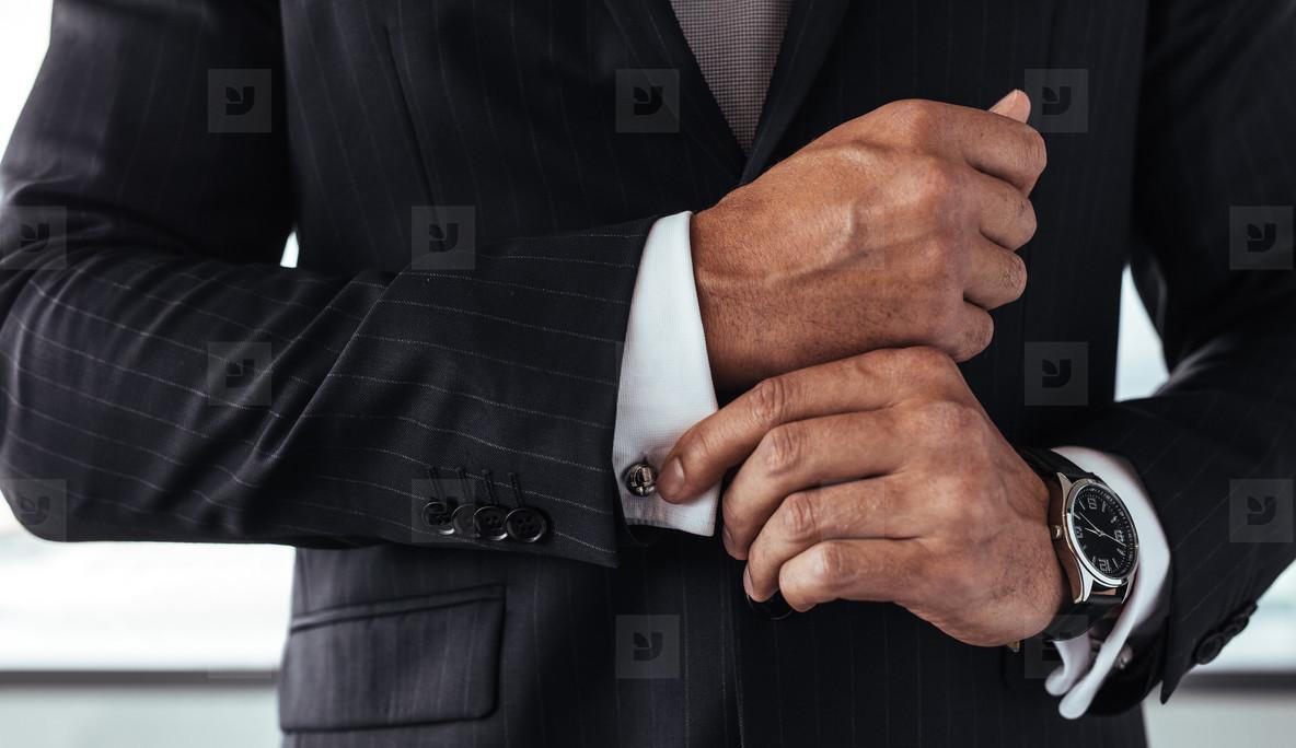Business man correcting a sleeve