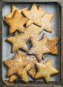 Christmas gingerbread cookies in shape of stars with sugar powder