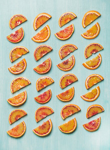 Fresh juicy blood orange slices placed in rows  blue background
