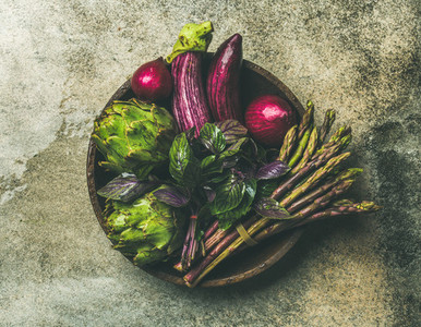 Flat lay of green and purple vegetables on plate grey background