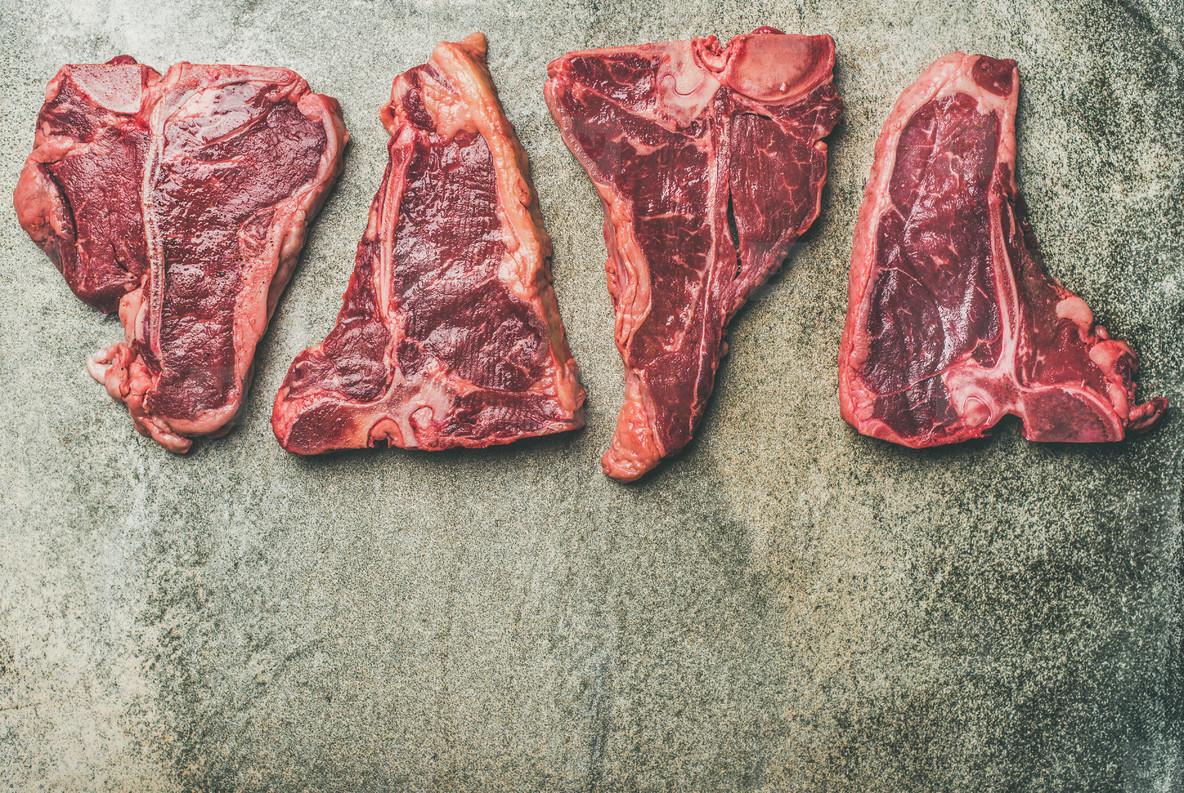 Porterhouse  t bone and rib eye steaks over grey concrete background