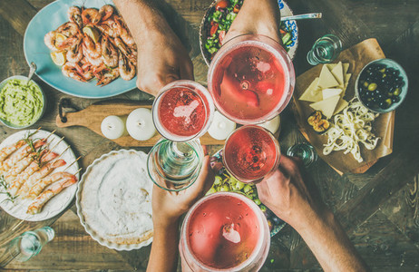 Flat lay of friends hands eating and drinking together  horizontal composition