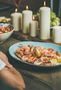 Salad shrimps and candles on wooden table