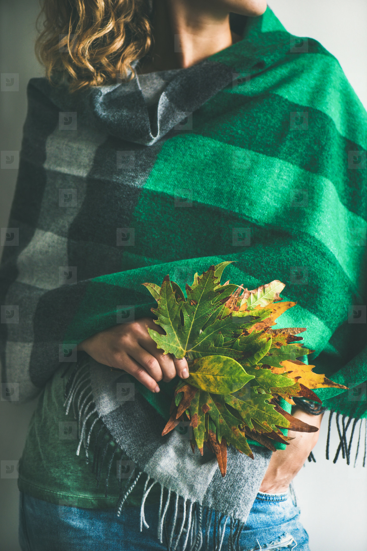 Woman in warm scarf or blanket with Autumn leaves