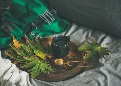 Black mug of tea with sieve and leaves on tray
