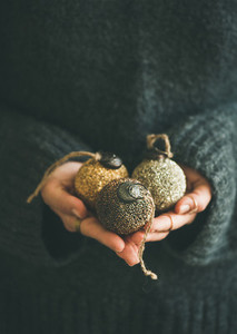 Woman holding golden and silver balls in hands vertical composition