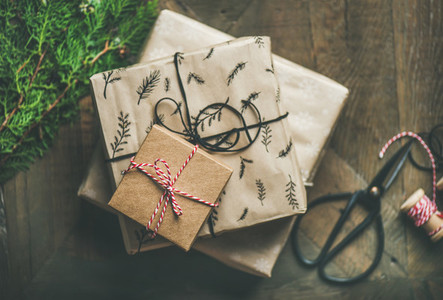 Gift boxes  fur tree branches  rope  scissors over wooden background