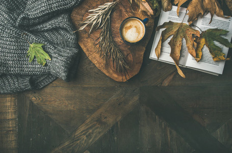 Autumn morning coffee concept with leaves jamper and book