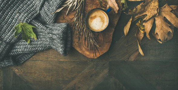 Autumn morning coffee concept with leaves and sweater copy space