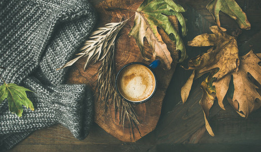 Autumn morning coffee concept with leaves and woolen sweater