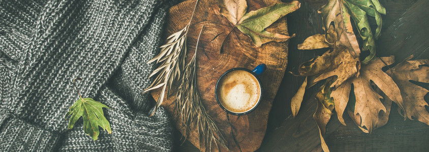 Autumn coffee concept with leaves and grey sweater  wide composition