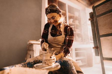 Female potter making clay pot