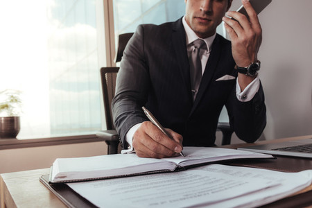 Businessman talking on mobile phone and making notes