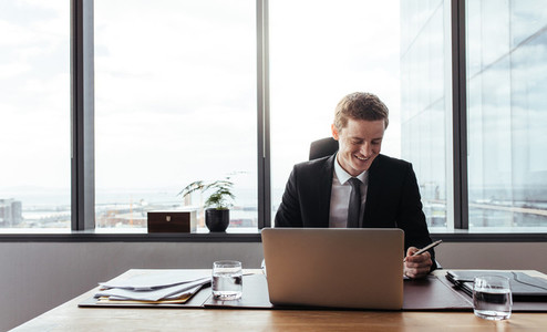 Businessman working at his desk and smiling