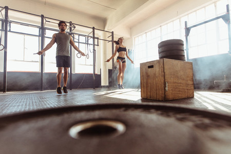 Fit couple jumping ropes in cross training gym