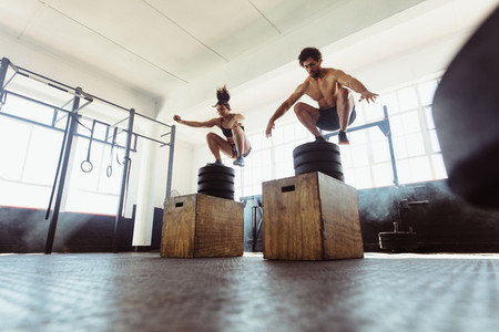 Healthy man and woman box jumping at gym