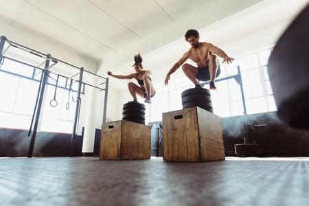Healthy man and woman box jumping at gym