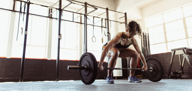 Healthy young woman lifting a barbell