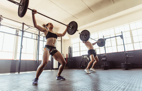 Man and woman doing weightlifting exercises in gym