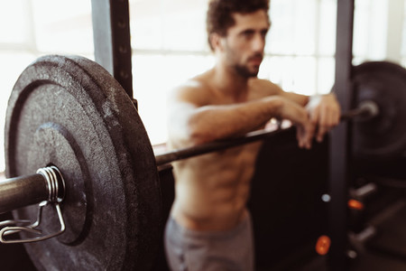 Muscular man leaning over barbell