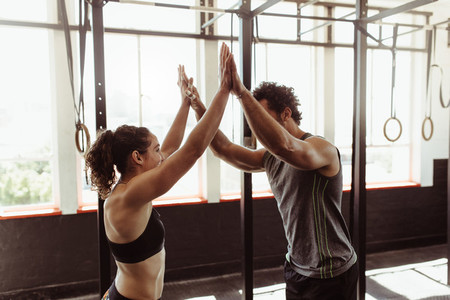 Fit couple high fiving at the gym