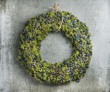 Christmas decorative wreath with bilberries over grey concrete wall background