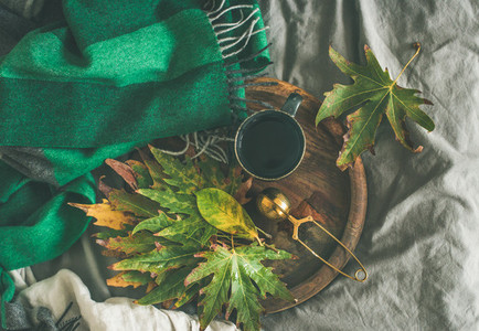 Mug of tea with sieve and autumn leaves  top view