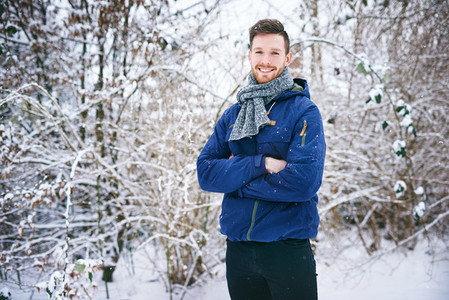 Young man smiling on snowy forest background