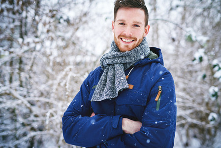 Laughing man in coat on snowy background