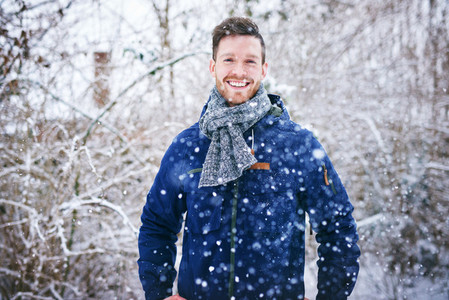 Young handsome man in snowfall smiling cheerfully