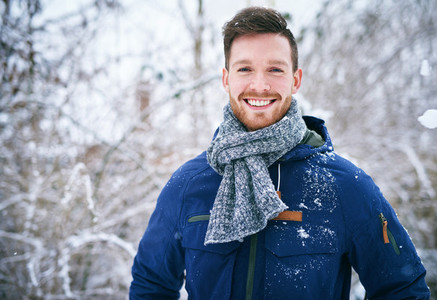 Young man in coat standing in snowfall
