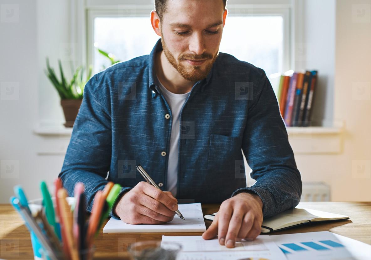 Man checking notes at home office