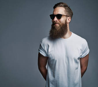 Bearded handsome man with sunglasses looking over