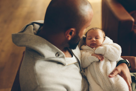 Newborn baby boy in his father039 s arms