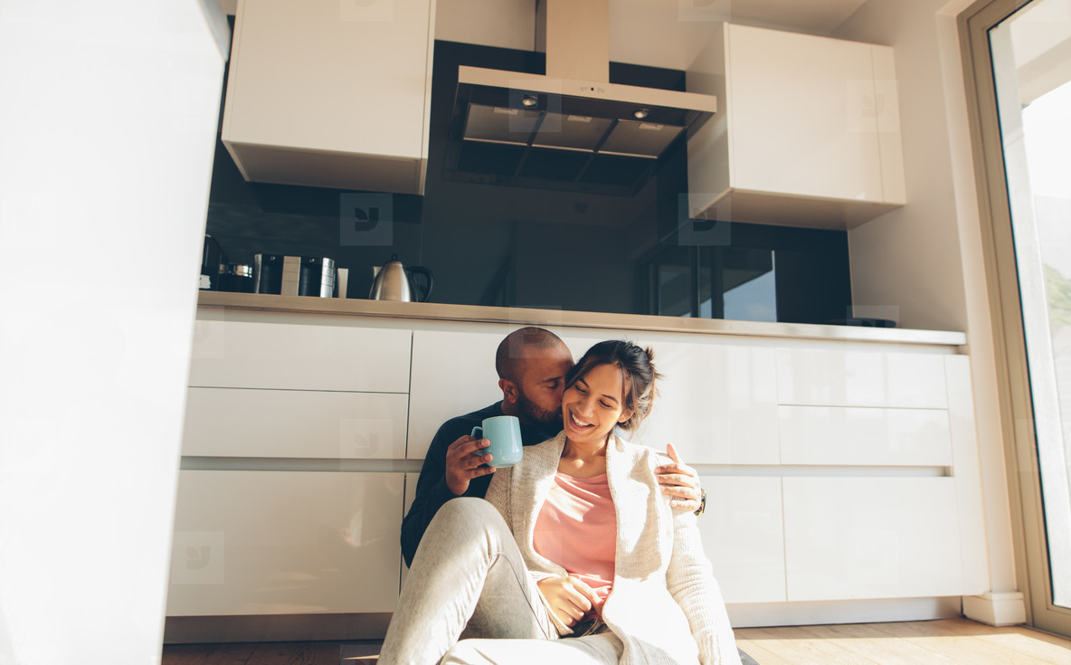 Romantic young couple sitting on kitchen floor