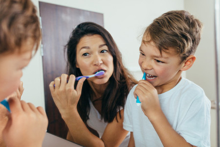 Mother and son brushing teeth in bathroom