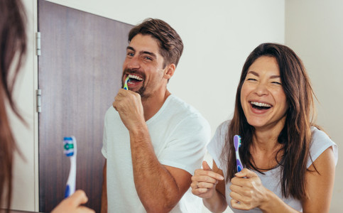 Smiling couple brushing teeth in bathroom