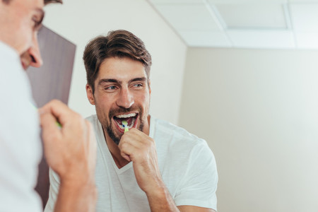 Man brushing teeth in the bathroom