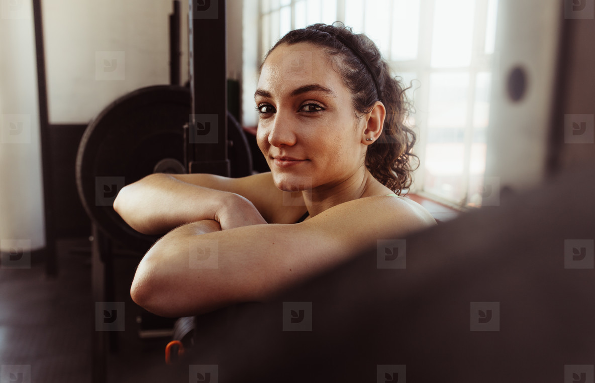 Woman leaning over barbell after workout