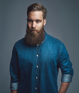 Bearded man in blue denim with serious expression